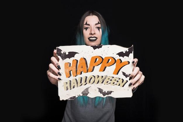 Mujer sujetando papel con lettering de halloween
