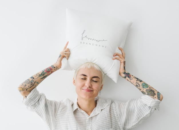 Mujer tatuada sosteniendo una maqueta de almohada femenina sobre su cabeza