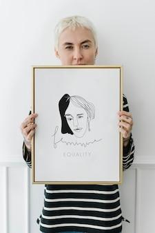 Mujer tatuada sosteniendo una maqueta de marco de fotos en blanco