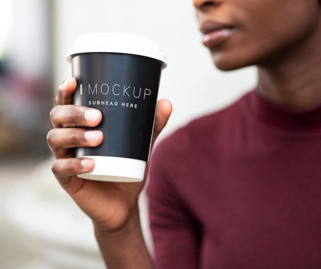 Mujer tomando café en una taza de papel maqueta