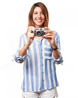 Mujer usando su cámara antigua con una gran sonrisa