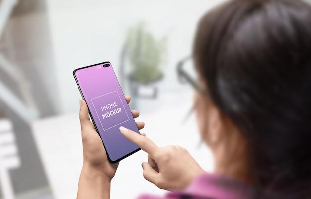 Mujer usar maqueta de teléfono. chica toca la pantalla del teléfono con la mano derecha