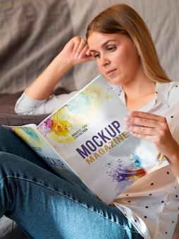 Mujer vestida casual leyendo una revista simulada