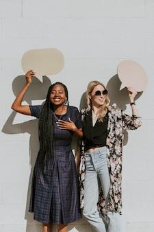 Mujeres alegres que muestran burbujas de discurso en blanco