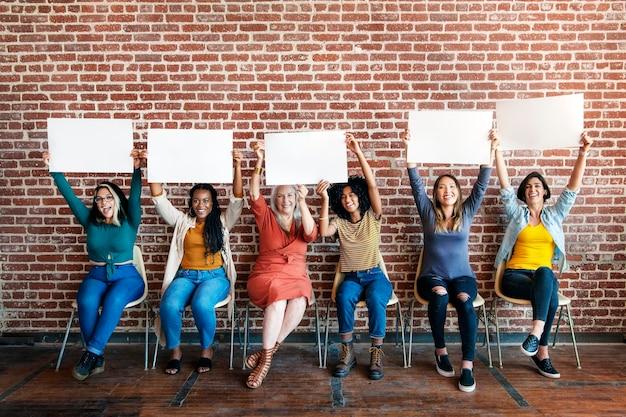 Mujeres diversas que muestran la plantilla de carteles en blanco