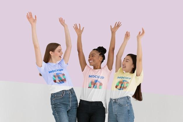 Mujeres jóvenes que representan el concepto de inclusión con maquetas de camisetas