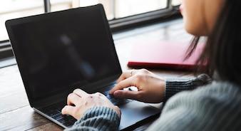 Mulher, usando computador portátil, escrivaninha