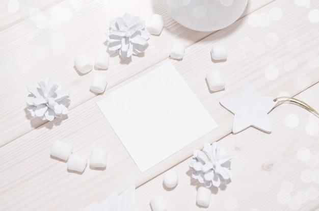 Navidad con maqueta de tarjeta cuadrada y decoraciones blancas en mesa de madera