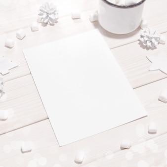Navidad con maqueta de tarjeta y decoraciones blancas en mesa de madera