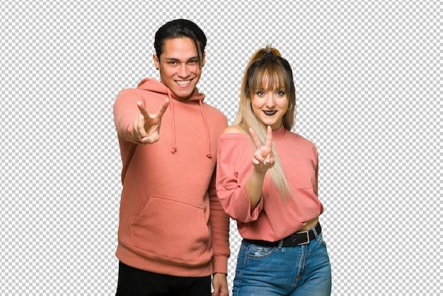 Nel giorno di san valentino coppia giovane sorridente e mostrando il segno della vittoria