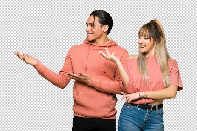 Nel giorno di san valentino giovane coppia che estende le mani a lato per invitare a venire