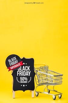 Nero venerdì mockup con carrello di shopping accanto a bordo