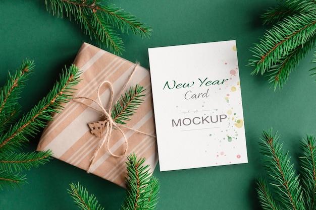 Nieuwjaars- of kerstwenskaartmodel met geschenkdoos en groene dennenboomtakken