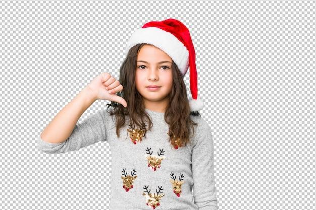 Niña celebrando el día de navidad mostrando un gesto de aversión, pulgares hacia abajo. concepto de desacuerdo