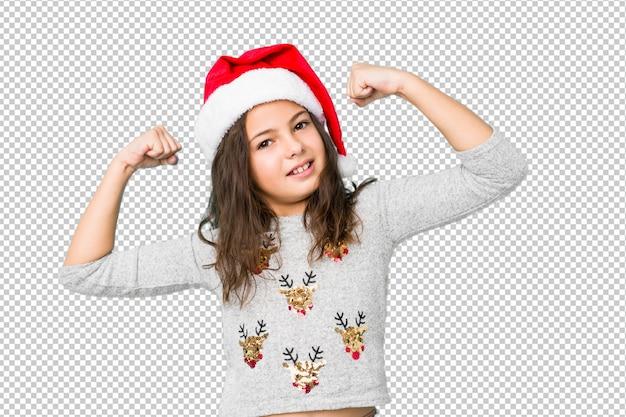 Niña celebrando el día de navidad mostrando un gesto de fuerza con los brazos, símbolo del poder femenino