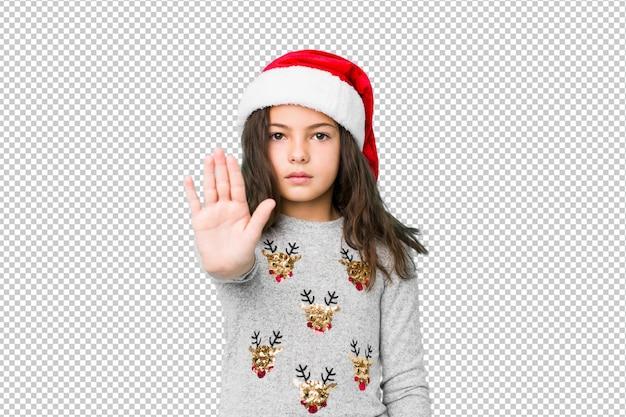 Niña celebrando el día de navidad de pie con la mano extendida que muestra la señal de stop, impidiéndole.