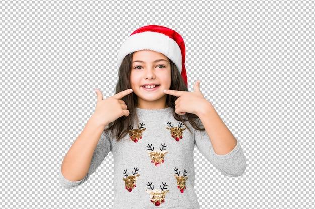 Niña celebrando el día de navidad sonríe, señalando con el dedo en la boca.