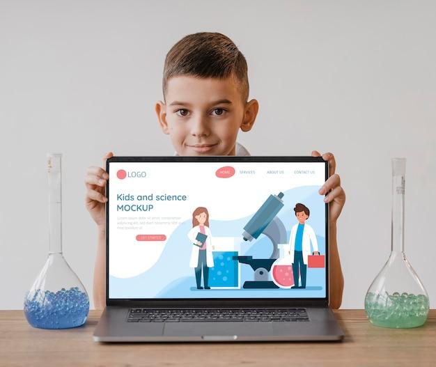 Niño en clase de ciencias con maqueta de laptop