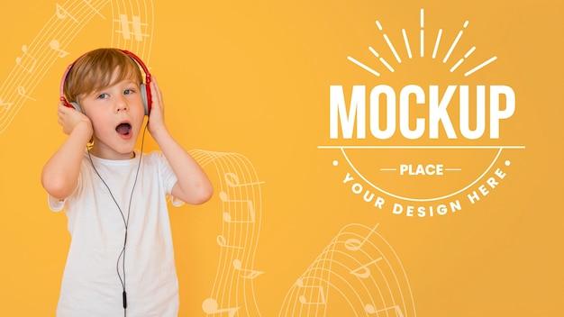Niño escuchando música a través de auriculares con maqueta de fondo