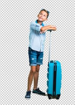 Niño con gafas de sol y auriculares que viajan con su maleta de pie y mirando hacia arriba.