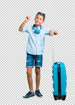 Niño con gafas de sol y auriculares viajando con su maleta de pie y pensando en una idea.