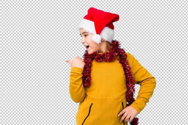 El niño pequeño que celebra el día de navidad que lleva un sombrero de santa aisló puntos con el dedo pulgar lejos, riendo y despreocupado.