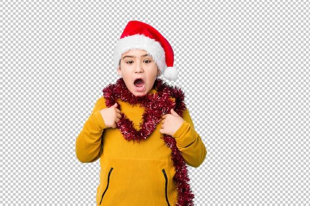 El niño pequeño que celebraba el día de navidad con un sombrero de santa aislado sorprendió señalar con el dedo, sonriendo ampliamente.