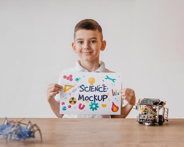Niño sosteniendo una maqueta de tarjeta mientras aprende ciencias