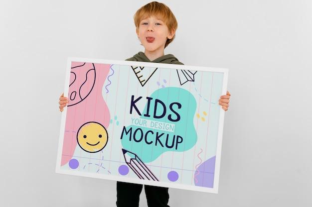 Niño talentoso sosteniendo un dibujo de maqueta