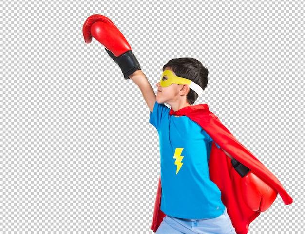 Niño vestido de superhéroe con guantes de boxeo.