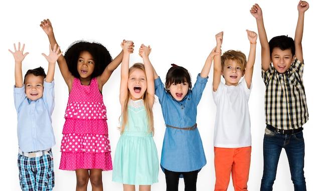 Niños pequeños con las manos arriba