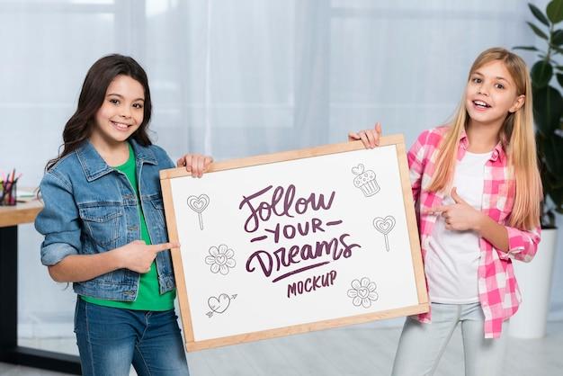 Niños positivos con cartel de maqueta