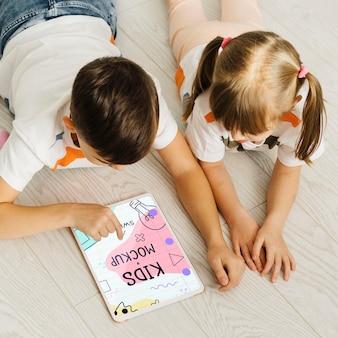 Niños de tiro medio en el piso con tableta