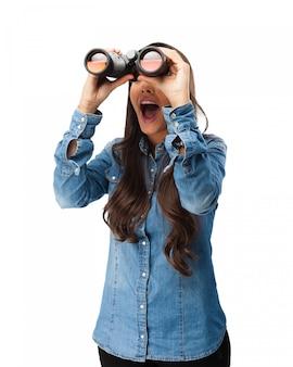 Nosy jonge vrouw met een verrekijker