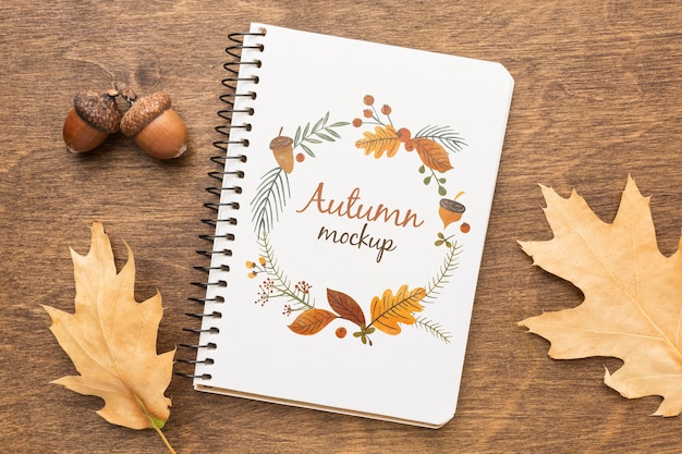 Notebook con ghiande e foglie accanto