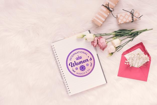 Notebook mock-up con fiori e regali