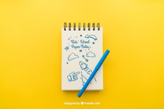 Notitieblok met potlood op gele achtergrond