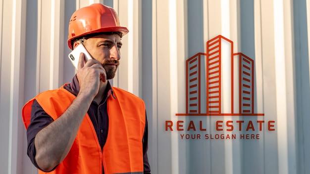 Onroerende goederenmens met bouwvakker die op telefoon spreken