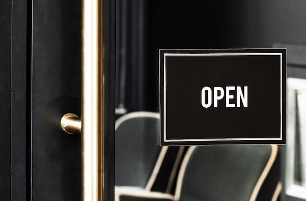 Open sign mockup sulla porta di un caffè