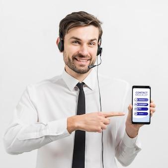 Operador de centro de llamadas que muestra un teléfono móvil de maqueta