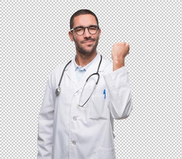 Orgulloso doctor joven con su puño arriba
