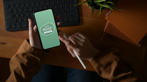 Overhead schot van vrouwelijke hand texting op mock-up smartphone op houten tafel