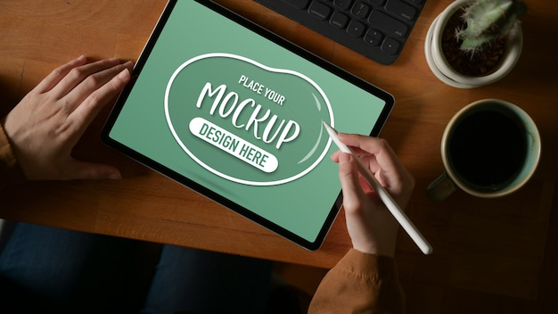 Overhead schot van vrouwelijke handen bezig met mock-up tablet met stylus op houten tafel