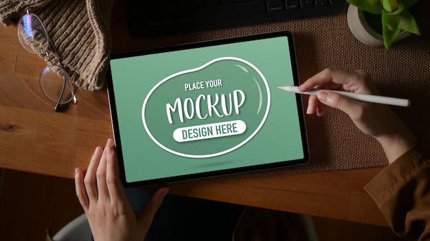 Overhead schot van vrouwelijke handen met behulp van mock-up digitale tablet op houten werktafel