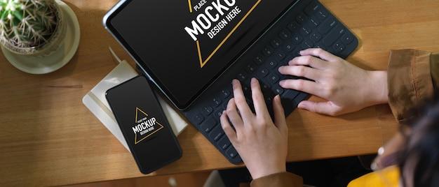 Overhead schot van vrouwelijke werken met mock-up digitale tablet, smartphone en schemaboek