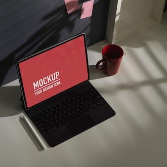 Overhead schot van werktafel met tabletmodel, koffiemok en pen