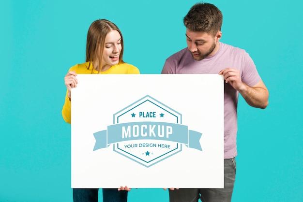 Paar dat een mock-upkaart voor briefpapier houdt