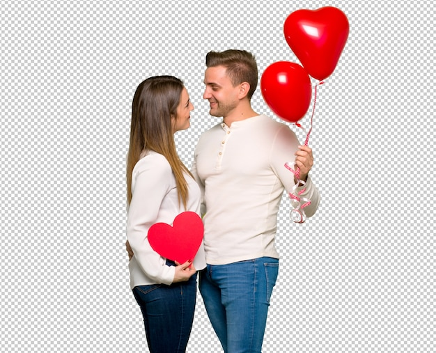 Paar dat in valentijnskaartdag een hartsymbool en ballons houdt