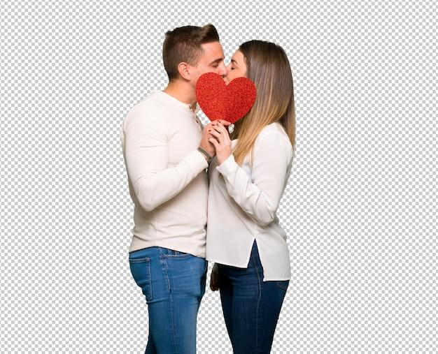 Paar dat in valentijnskaartdag een hartsymbool en het kussen houdt