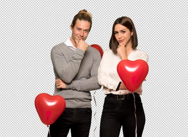 Paar dat in valentijnskaartdag en aan de voorzijde met zeker gezicht glimlacht kijkt